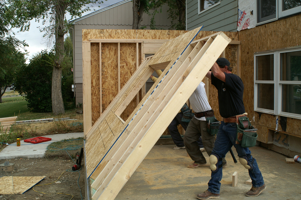 a team of two contractors lifting up a wall for a home addition